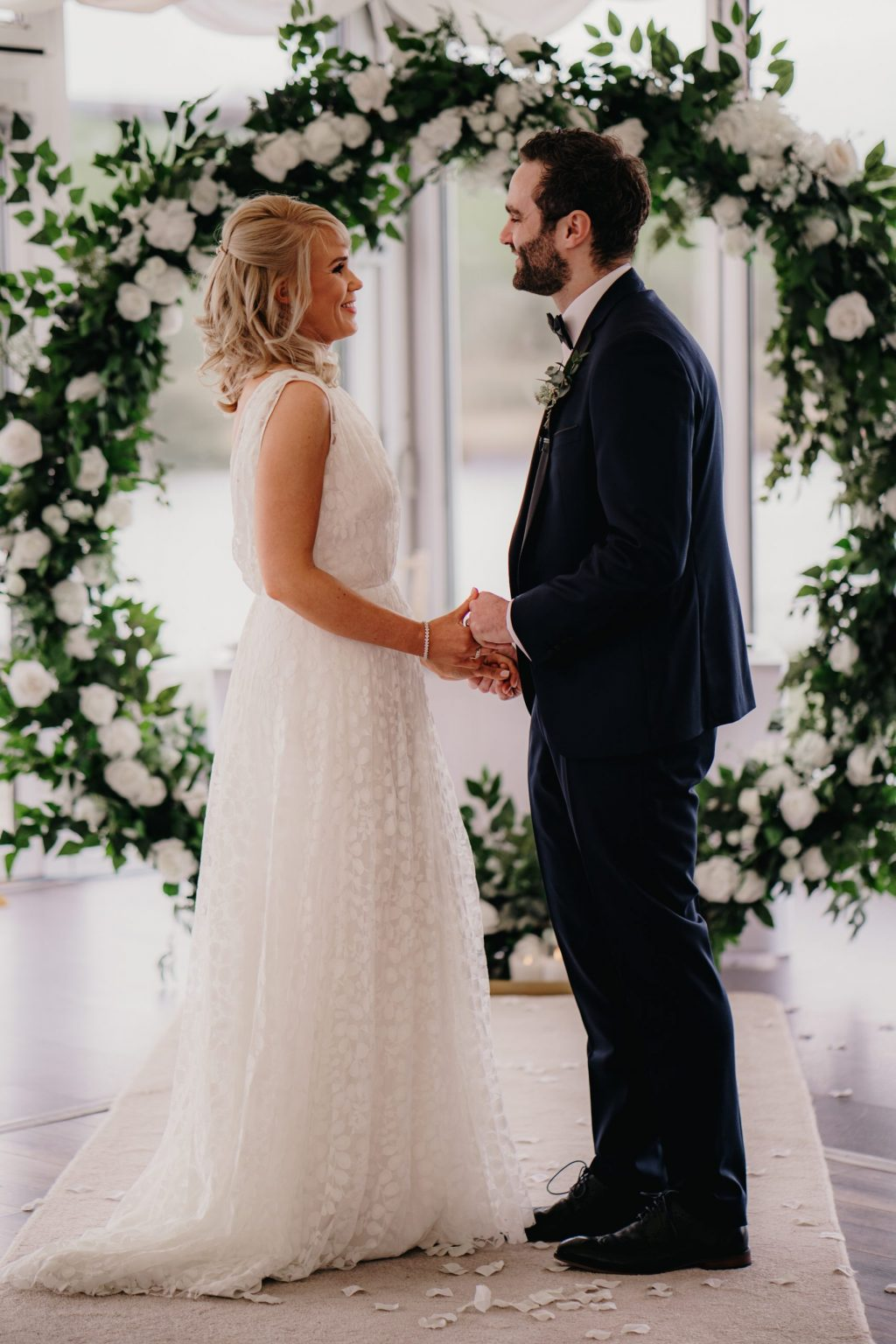bride and groom standing in front of a floral hoop saying their vows