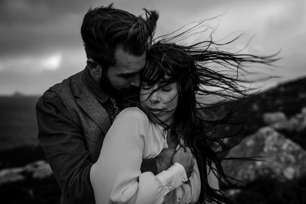 black and white image of couple embracing. hair blowing in the wind