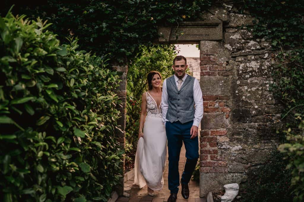 bride and groom walking through an archway