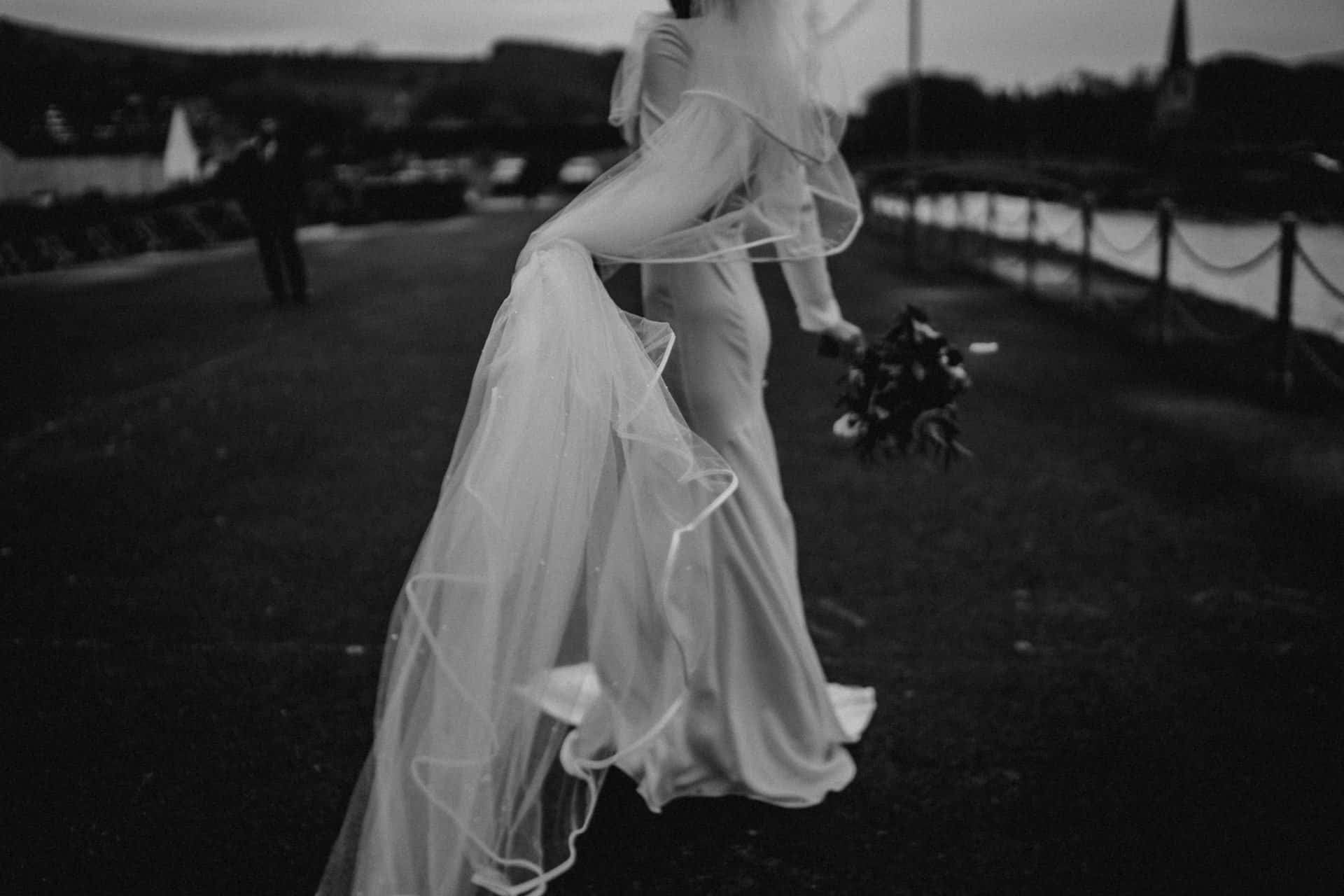 black and white image of a bride holding her veil and it blowing in the wind