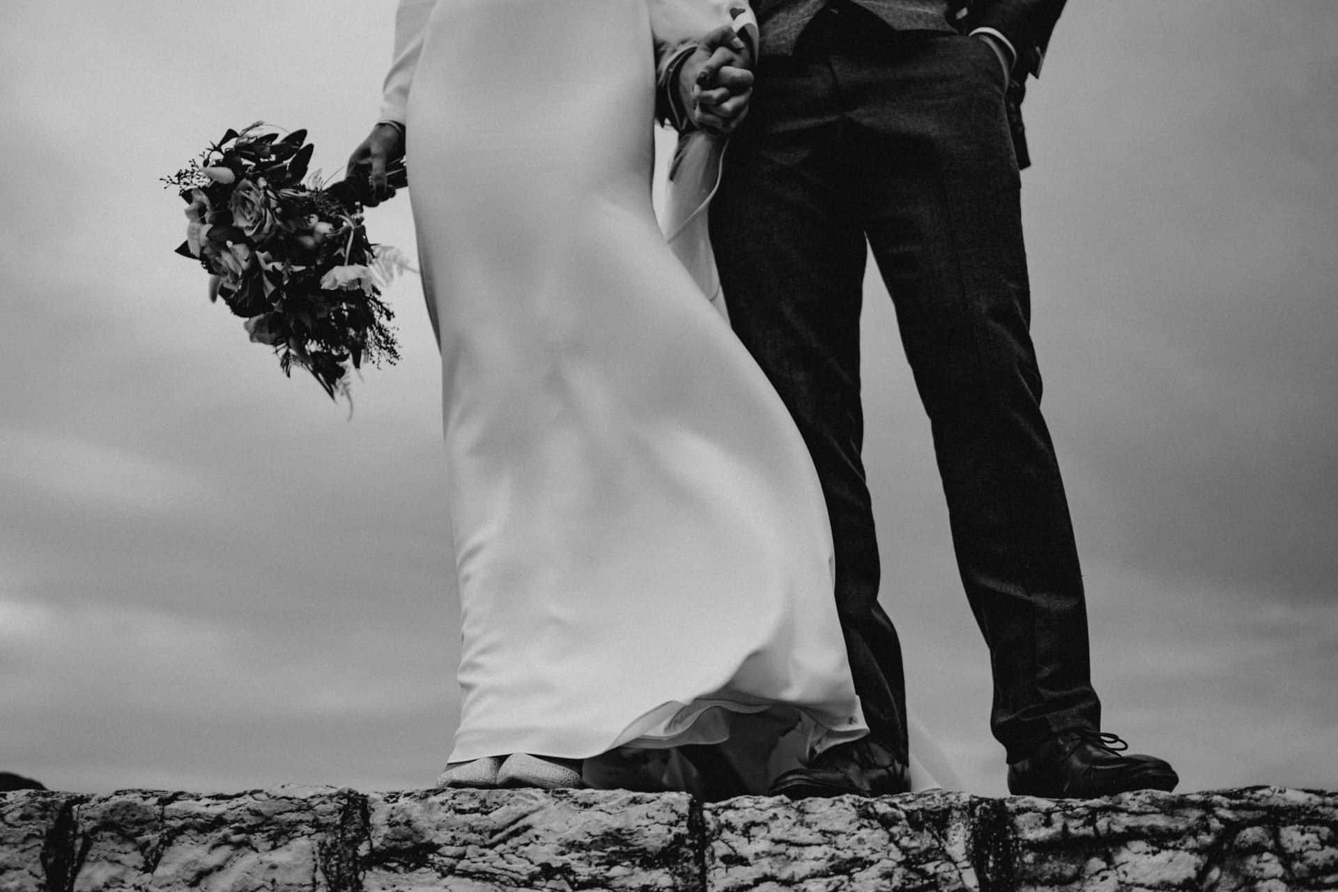 black and white image of a couple standing on a wall